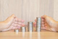 Monete o soldi impilati per il grafico crescente con le mani Fotografia Stock Libera da Diritti