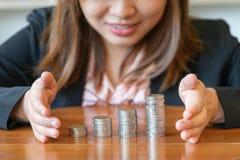 Monete o soldi impilati per il grafico crescente con le mani Immagine Stock Libera da Diritti