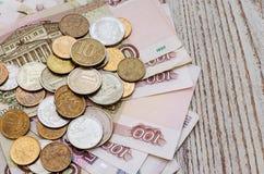 Monete russe sui precedenti della banca russa delle banconote di carta Immagini Stock