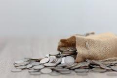 Monete in sacco sulla tavola di legno immagini stock