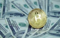 Monete simboliche di bitcoin sulle banconote di cento dollari Fotografia Stock