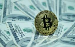 Monete simboliche di bitcoin sulle banconote di cento dollari Fotografie Stock Libere da Diritti