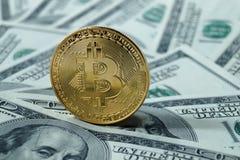 Monete simboliche di bitcoin sulle banconote di cento dollari Immagine Stock