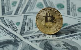 Monete simboliche di bitcoin sulle banconote di cento dollari Fotografia Stock Libera da Diritti