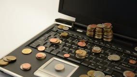 Monete su un computer portatile isolato su fondo bianco stock footage