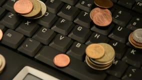 Monete su un computer portatile isolato su fondo bianco video d archivio