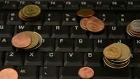 Monete su un computer portatile isolato su fondo bianco archivi video