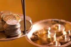 Monete su un peso della scala Immagini Stock Libere da Diritti
