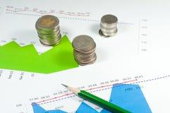 Monete sul fondo dei grafici e dei grafici di verde blu con la matita Mo Fotografie Stock Libere da Diritti