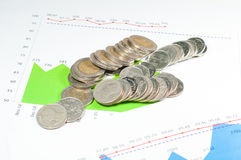 Monete sul fondo dei grafici e dei grafici di verde blu soldi e fina Fotografia Stock Libera da Diritti
