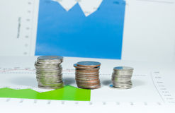 Monete sul fondo dei grafici e dei grafici di verde blu soldi e fina Immagine Stock