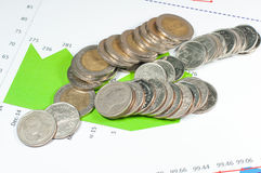 Monete sul fondo dei grafici e dei grafici di verde blu soldi e fina Fotografie Stock Libere da Diritti