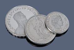 Monete svizzere su un fondo grigio Immagini Stock