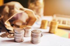 Monete tailandesi Soldi tailandesi Monete impilate su a vicenda nelle posizioni differenti con il calcolatore immagini stock