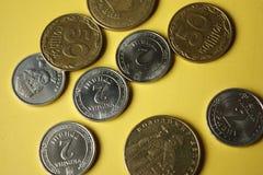 Monete ucraine isolate su fondo giallo Le monete del primo piano sono situate nel centro del telaio Immagine concettuale fotografia stock