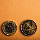 Monete un e due euro su un fondo di cartone Fotografia Stock