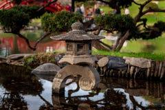Monete in un piccolo stagno giapponese con le riflessioni fotografia stock