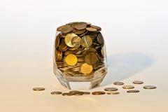Monete in un vetro Immagini Stock