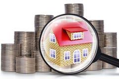 Monete, una casa e una lente d'ingrandimento Immagini Stock