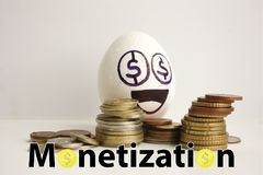 Monetization concept. funny and. Funny eggs with a face. among the gold coins Stock Image