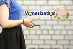 Monetization concept. income from. A hobby. young woman with smart phone on brick wall background Royalty Free Stock Images