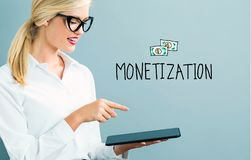 Monetization text with business woman. Using a tablet stock photo