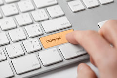Monetize on-line. Internet project concept. Freelancer (e-nomad, digital nomad) revenue his microbusiness startup - click on keypad monetize on keyboard Stock Image