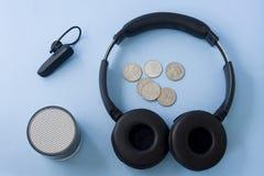 Monety, bezprzewodowa słuchawki, hełmofony i mówca na błękitnym pastelu, ja zdjęcie stock