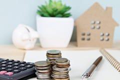Monety brogują i kalkulator przed drewnianego domu modelem i prosiątko bankiem obraz royalty free