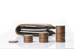 Monety broguje up w wykresu kształcie z portflem w tle Zdjęcia Stock