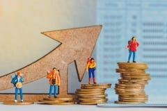 Monety i grupa podróżnik miniatury mine postacie z na paszporcie plecaka odprowadzeniem i stojakiem zdjęcie stock