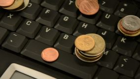 Monety na laptopie odizolowywającym na białym tle zbiory