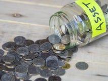 Monety nalewa z szklanego słoju z etykietką Fotografia Stock