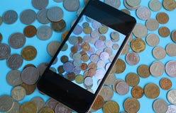 Monety rozpraszają na stole i tam jest telefon na one obrazy royalty free