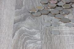 Monety są na drewnianym szarość stole fotografia stock