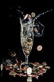 Monety spada w szampańskiego szkło Obraz Royalty Free