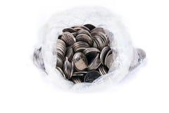 Monety w plastikowym worku odizolowywającym na bielu Fotografia Royalty Free
