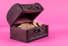 Monety w starym drewnianym pudełku na różowym tle Obrazy Stock