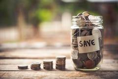 Monety w szklanym słoju dla pieniądze oszczędzania finanse i inwestyci conce zdjęcia stock