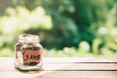 Monety w szklanym słoju z słowa save monet pojęcia ręk pieniądze stosu chronienia oszczędzanie Fotografia Royalty Free