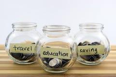 Monety w szklanym zbiorniku z podróżą, oszczędzania i edukaci etykietki zdjęcie royalty free