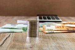 Monety zamykają w górę tła euro, dolary i kalkulator dalej, obrazy stock