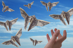Money. A hand trying to catch dollar bills shaped like butterflies. A blue sky serves as the background royalty free stock image