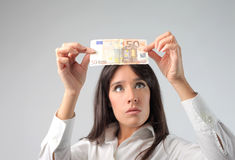 Money. Woman controlling a euro banknote Stock Photography