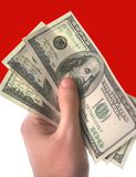 Money. Holding dollars in hand on red-white background Royalty Free Stock Photo
