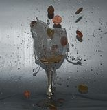 Money. Small coins in the glass of wine Royalty Free Stock Photo