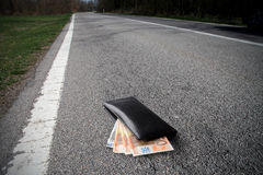 Money. Wallet with some banknotes in it lying on a countryside road Stock Photography