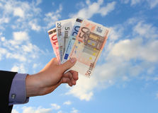 Money. A business hand holding money in front of cloudy sky Royalty Free Stock Photo