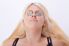Money. Two coins are placed on the eyes of a young woman royalty free stock image