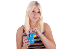 Money. A young woman puts a note in a piggy bank stock image